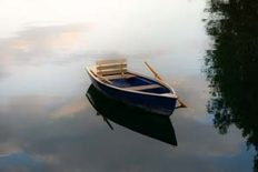 Image of wooden rowing boat on lake, moody tones