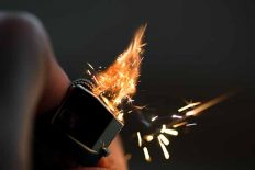 Lighters with flame sparking on dark background. Selective focus and shallow depth of field.